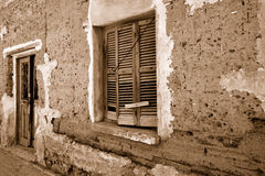 Old grungy wall. Fragment wall of old abandoned building with cracked door and window. Sepia Stock Photography