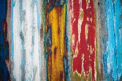 Old grungy weathered colourfully painted wooden wall plank texture in yellow, blue, red and white color mix artistic background. Old grungy and weathered Royalty Free Stock Photography