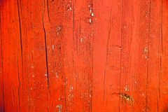Old grungy and weathered red and orange painted wooden wall plank texture background. Marked by long exposure to the elements outdoors and with paint coating Royalty Free Stock Photography