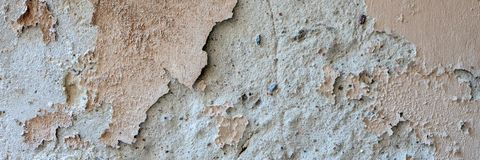 Old grungy weathered wall background texture. Beige dirty peeled plaster wall with falling off flakes of paint stock photo
