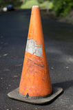 Old grungy worn out traffic cone on tarred road Stock Photography