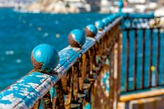 Old guardrail. Rusty blue guardrail on the sea front, in the french city of Marseille Royalty Free Stock Image
