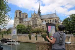 Painter painting in Paris cathedral Notre dame Royalty Free Stock Image