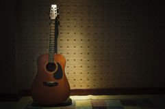 old guitar against vintage wall Royalty Free Stock Photos