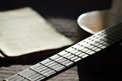 The old guitar and music books lit by the sun Stock Image