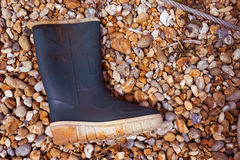 Old gumboot washed up on a stony seashore Royalty Free Stock Photo