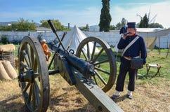 Old gun. Balaklava, Crimea - September 30: Gunner stand near the old gun on September 30, 2017  in Balaklava, Crimea Stock Image