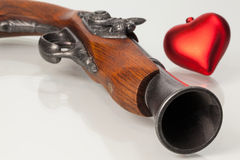 Old gun and red heart Royalty Free Stock Photo