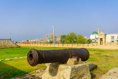 Old guns on the city wall promenade in Acre Akko. ACRE, ISRAEL - APRIL 27, 2017: Old guns on the city wall promenade, with a visitor and other monuments, in Acre Stock Photos