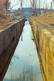 Old gutter. Channel empties into the river Royalty Free Stock Photo