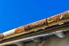 Old gutter. A broken gutter on the roof of a house Royalty Free Stock Photo