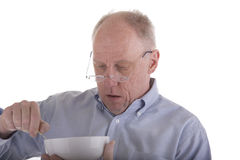 Old Guy in Blue Eating Cereal Stock Photos