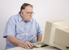 Old guy on computer. Older man surfing the web royalty free stock photography
