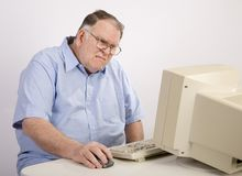 Old Guy at computer grimacing. Older male working on computer and grimacing royalty free stock images