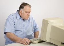 Old guy at computer not happy. Older man surfing the net and not happy royalty free stock photography