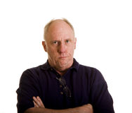 Old Guy Looking Impatient. An older bald man in a blue shirt with arms crossed looking angry or impatient stock photo
