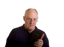 Old Guy Looking Over Glasses with Bible. An older bald man holding a bible and looking over his reading glasses Stock Images