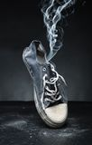 Old gym-shoe  in smoke Stock Image