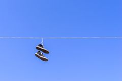 Old gym shoes on a wire against the blue sky Stock Image