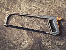 Old hacksaw on concrete grungy background Royalty Free Stock Image
