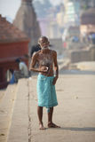 Old hairy indian man drinking tea at river Ganges, Royalty Free Stock Photos