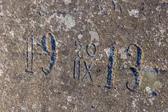 Old half-erased inscriptions, embossed on a granite rock. Abandoned quarry in the Ladoga skerries, Karelia, Russia. Sunny day in early June Stock Image