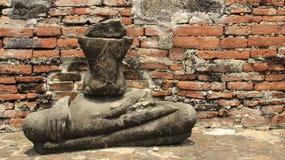 Old Half Stone Buddha Statue With Bricks Walls. Ancient stone Buddha with brick walls and sunlight.  Ruins And Historical Park in Ayutthaya Thailand royalty free stock photo