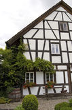 Old Half-Timbered House. Antique restored half-timbered European private house, partially overgrown by a climbing plant Royalty Free Stock Photos