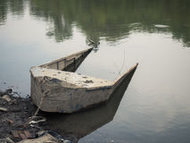 An old halfsunken fishing boat on the river shore. Royalty Free Stock Photography