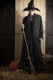 Old halloween witch with broom and pumpkin. In a barn royalty free stock images