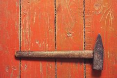 Old hammer on an old brown wooden background. Old hammer on old brown wooden background Royalty Free Stock Image
