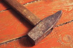Old hammer on an old brown wooden background. Old hammer on old brown wooden background Royalty Free Stock Photos