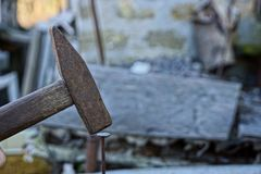 Old hammer hammering a nail into a wooden board. Clogging with a rusty old nail hammer Royalty Free Stock Photography