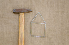 Old hammer and house made ??of nails linen texture Stock Photo