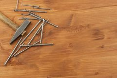Old hammer and nails, piles of various sizes. Vintage old hammer with rusty nails. Tools on a wooden background. Stock Photos