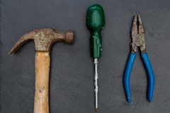 Old hammer screwdriver and pliers DIY tools. On dark background stock images