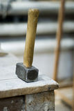 Old used hammer on a wooden background Stock Image