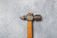An old hammer on a wooden handle. Gray concrete background.  stock image