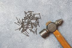 An old hammer on a wooden handle and nails. Gray concrete background.  stock photography