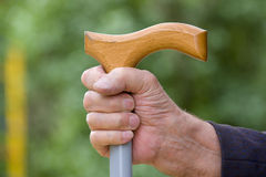 Old hand. With a cane on a green background Royalty Free Stock Images