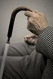 Old Hand. An old man holding his walking stick while standing on the bench Stock Photography