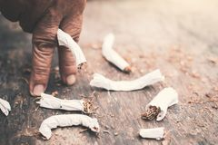 Old hand crushing cigarettes stock photos