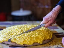 Old hand cutting polenta stock photography