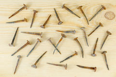 Old hand-forged nails which are chaotically lying on a board. Stock Photos