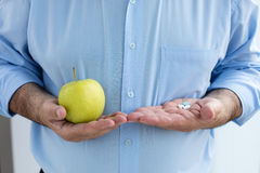 Old hand holding pills and apple Royalty Free Stock Images