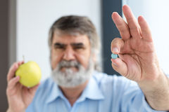 Old hand holding pills and apple Stock Image