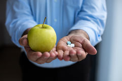 Old hand holding pills and apple Royalty Free Stock Image