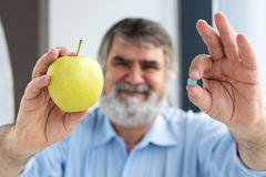 Old hand holding pills and apple Stock Photos