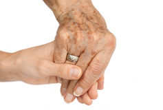 Old hand holding young hand. Isolated on white background Royalty Free Stock Photos