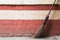 Old hand made street's broom against a brick wall Royalty Free Stock Photography